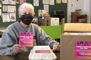 """A masked volunteer holds up a card reading """"We're Counting on You,"""" encouraging people to complete the 2020 US Census. The volunteer is wearing a mask to help prevent the spread of COVID-19."""